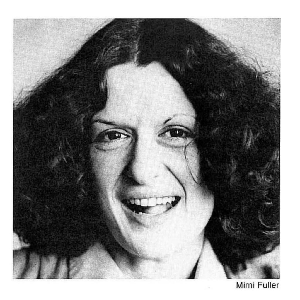 Photograph of Sandy Rosen, artist, headshot of a white woman with curly brown hair parted down the middle